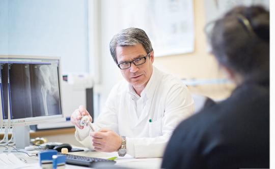 Prof. Andreas Roth – hier im Patientengespräch – leitet den Bereich Endoprothetik/Orthopädie. Mit dem Einsatz eines neuen Behandlungskonzepts wird er Patienten mit künstlichen Gelenken noch schneller als bisher wieder mobilisieren. Foto: Stefan Straube / UKL